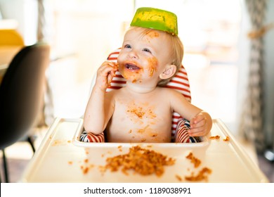 Little baby eating spaghetti dinner and making a mess