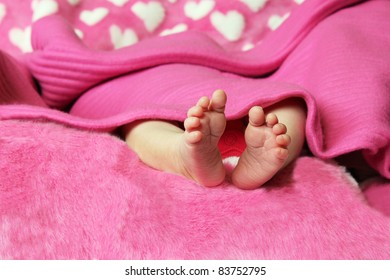 Little baby feet lying on pink fur blanket