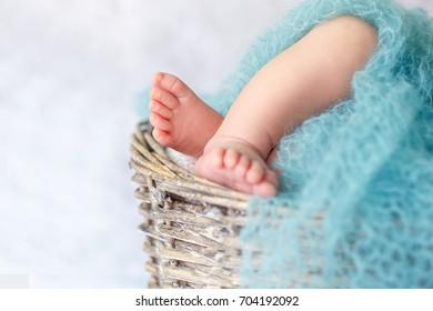 Little baby feet of a newborn baby sleeping in a wicker basket