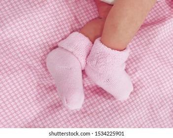 little baby feet in pink socks. newborn in socks on a pink sheet. cute baby legs. It's a girl. happy birthday daughters