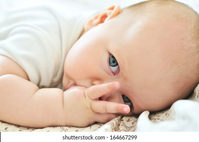 little baby with finger in mouth