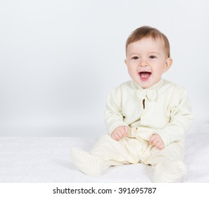 Little  baby funny boy in suit sitting. On white. Toddler baby laughs.  Little baby sitting on the bed.  Toddler funny.