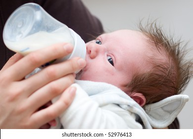 little baby get milk from a bottle with baby bib