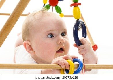 Little baby girl (6 months old) lying on the floor and playing with a toy bar, laughing at the camera, isolated against a white background.