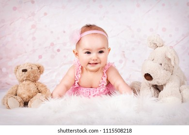 Little baby girl among plush toys