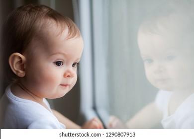 little baby girl with big dark eyes looking through the window