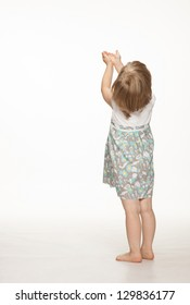 Little baby girl catching something, rear view; white background
