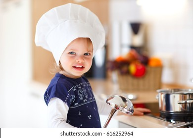 little baby girl with chef hat  inside the kitchen