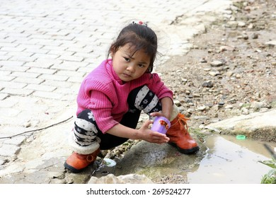 Little baby girl of Chinese hani minority plays in puddle on road. Remote village in South China. Yuanuang, China, February 25, 2013