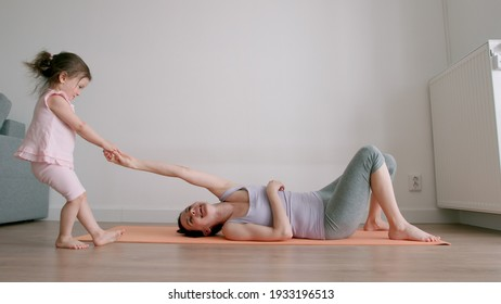 Little Baby girl disturbs his mother training of a yoga at home