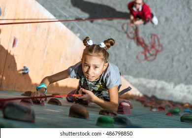 Little baby girl with funny hear style climbing vertical wall and man belaying her from below