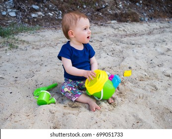 Little baby girl having some fun with her toys on a sadny beach of the Greek island of Thasos, Aegean sea.