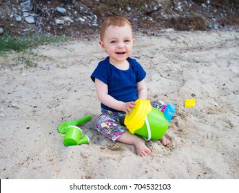 Little baby girl having some fun with her toys on a sandy beach of the Greek island of Thasos, Aegean sea.