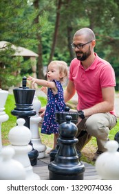 little baby girl and her father playing giant chess outside