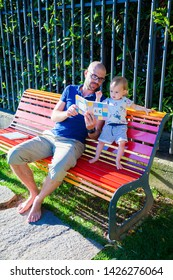 little baby girl and her father sitting on a bench in the park, reading an ABC-book