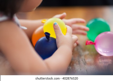 little baby girl hold colorful balls