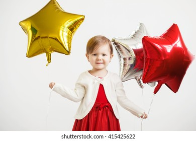 Little baby girl holding balloons in the form of stars. Young girl holding a star-shaped balloons. Happy child with colorful shiny foil balloons against a white background