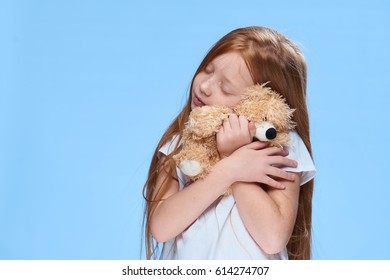 Little baby girl hugging a bear toy
