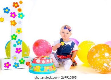 little baby girl isolated on white background with balloons near eats birthday cake sugar flower
