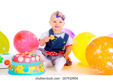 little baby girl isolated on white background with balloons near eats birthday cake sugar flower and laughs
