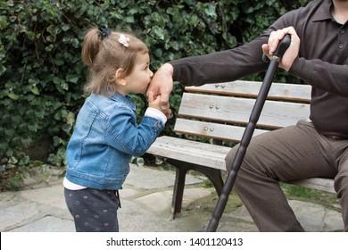 Little baby girl kiss her grandfather's hand during Eid mubarak (Turkish Ramazan or Seker Bayram). Adorable child kiss elderly man hand to show respect. Cute toddler follow muslim Ramadan traditions.