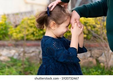 Little baby girl kiss her grandmother's hand during Eid mubarak (Turkish Ramazan or Seker Bayram). Adorable child kiss elderly woman hand to show respect. Cute toddler follow muslim Ramadan traditions - Shutterstock ID 1920732467
