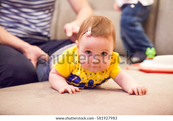 Little baby girl learning to crawl on the couch
