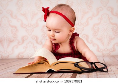 Little baby girl lying on the floor and reading a book with glasses and ribbon