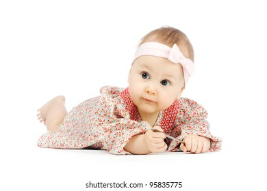 Little baby girl lying on the flor in dress on white background