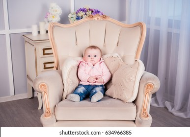A little baby girl is photographed in a beautiful outfit for 6 months