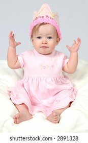 Little Baby Girl in Pink dress and birthday hat and hands in air