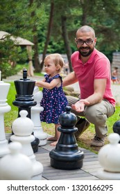 little baby girl playing giant chess outside, her father is surprised