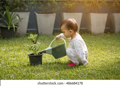 Little baby girl playing in green summer garden on sunny morning.