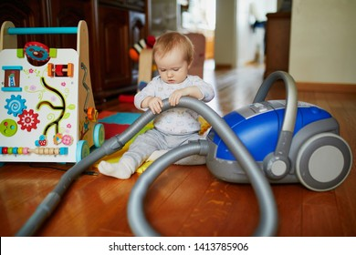 Little baby girl playing with vacuum cleaner at home. Toddler helping parents with chores.