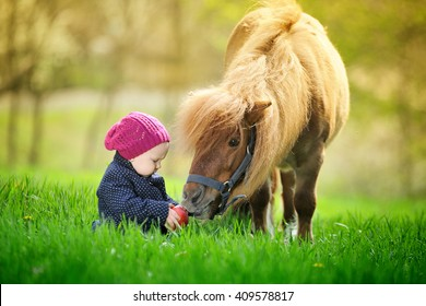 Little baby girl with red apple and pony
