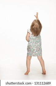 Little baby girl showing something above her, rear view; white background