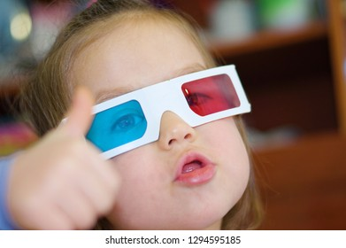 little baby girl showing super in 3D anaglyph cinema glasses for stereo image system with polarization. 3D googles with red and blue eyes