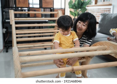 Little baby girl sit on pikler climbing toys with her mother while playing together in the house