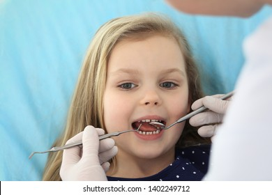 Little baby girl sitting at dental chair with open mouth and feeling fear during oral check up while doctor. Visiting dentist office. Medicine concept