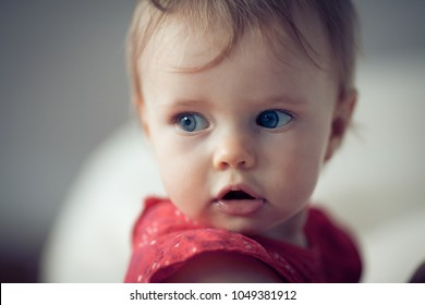 little baby girl sitting in front of a window