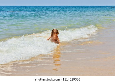Little baby girl sitting on the beach and playing in waves. Khao Lak beach. Thailand
