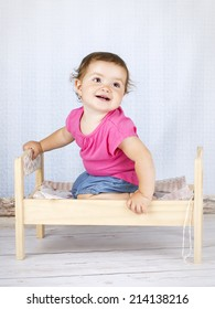 Little baby girl sitting on the small bed
