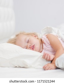little baby girl sleeping on a bed. Space for text