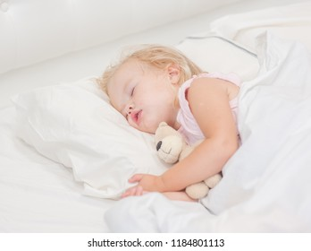 little baby girl sleeping on a bed with toy bear