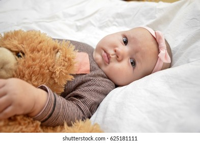 Little baby girl sleeping with plush toy. Teddy bear with baby.
