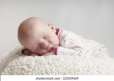little baby girl sleeps on a fur bad