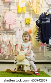 Little baby girl in store of toys