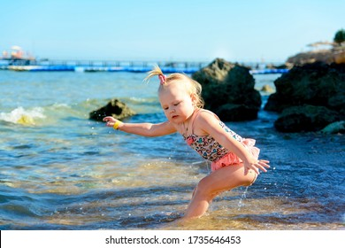 Little baby girl in swimsuit falls back into the water in the sea.