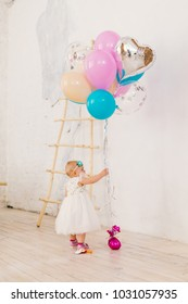 A little baby girl in white lavish dress is standing in living room in the house near the decorative staircase and stretches to bunch of brightly colored balloons. Concept of childrens birthday party.