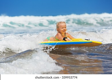 Little baby girl - young surfer with bodyboard has a fun on small sea waves. Active family lifestyle, people outdoor water sport lessons and swimming activity on surf camp summer vacation with child.